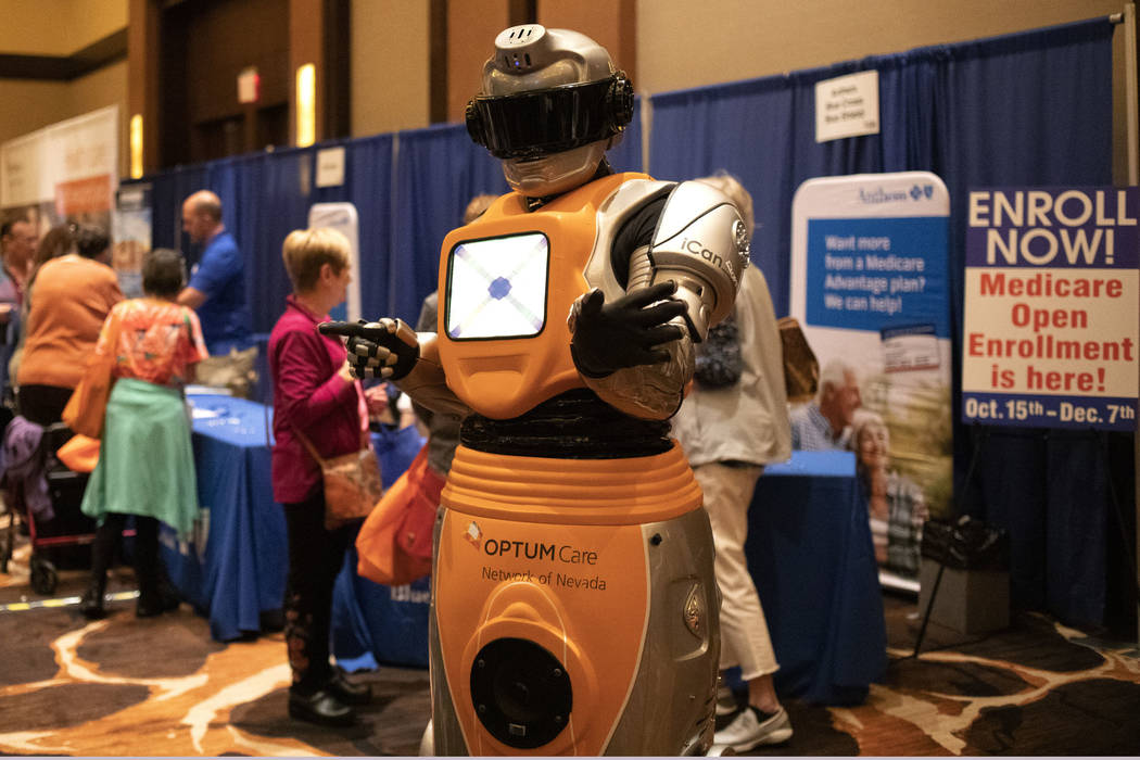 A robot brought by OptumCare interacts with attendants of the AgeWell Expo on Saturday, Nov. 9, ...