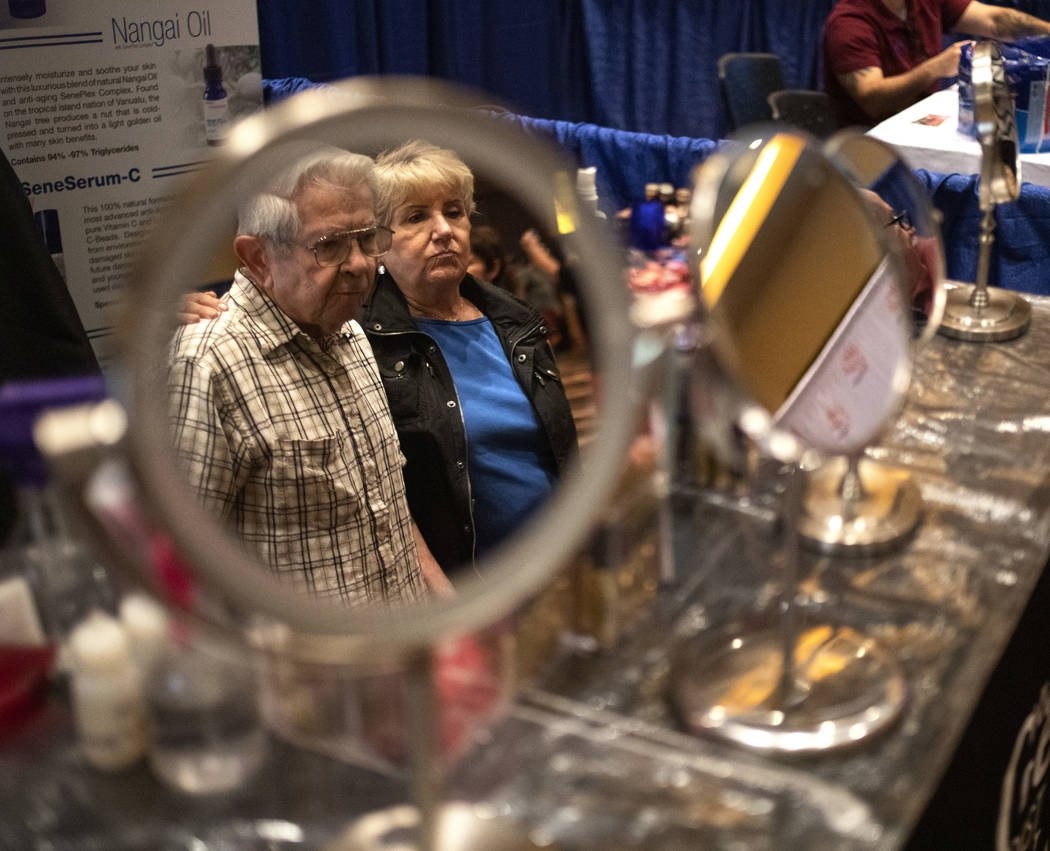 Marvin Labowitz, left, and Elna Fischer, right, are reflected in a mirrors during the AgeWell E ...