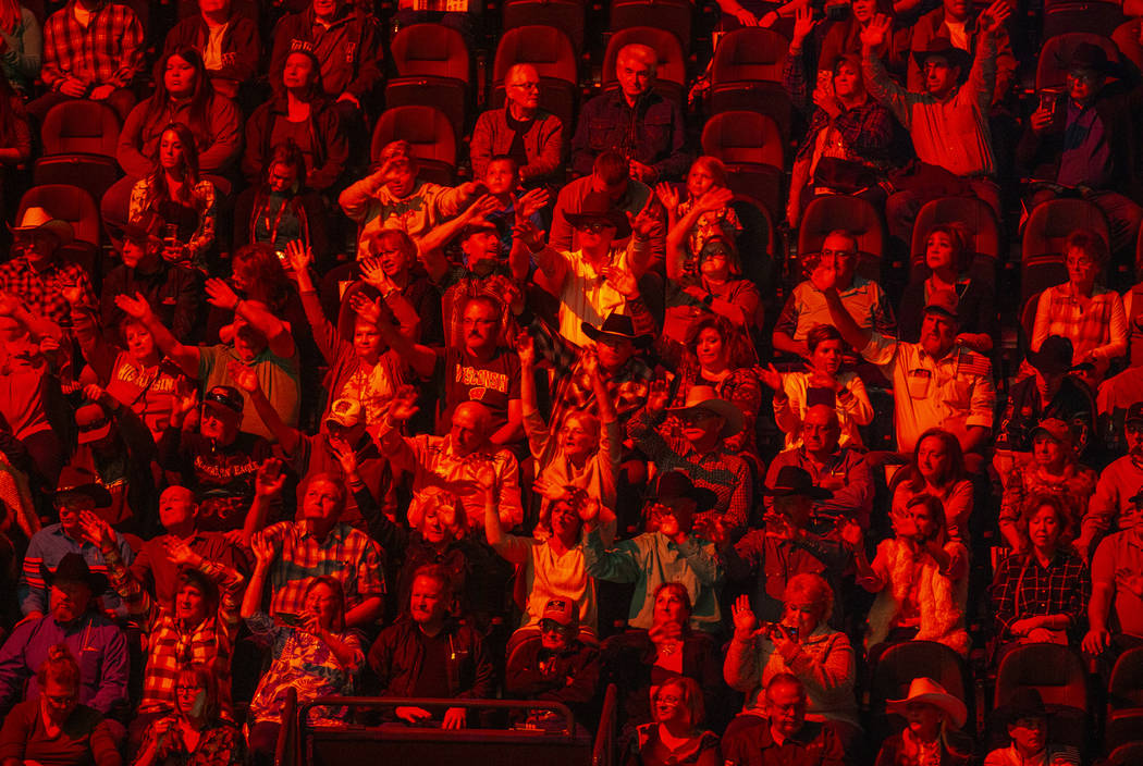 Fans are bathed in red as cowboys are announced during opening ceremonies on the third day of t ...