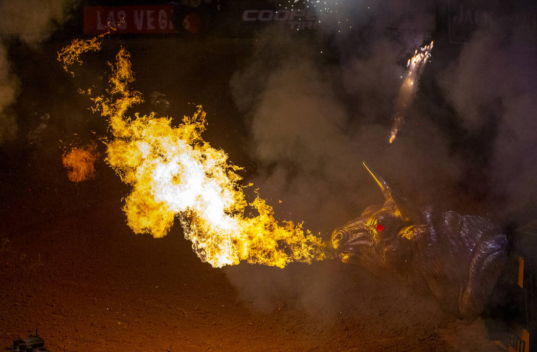 Flames erupt from a metal bull off the stage as cowboys are announced during opening ceremonies ...
