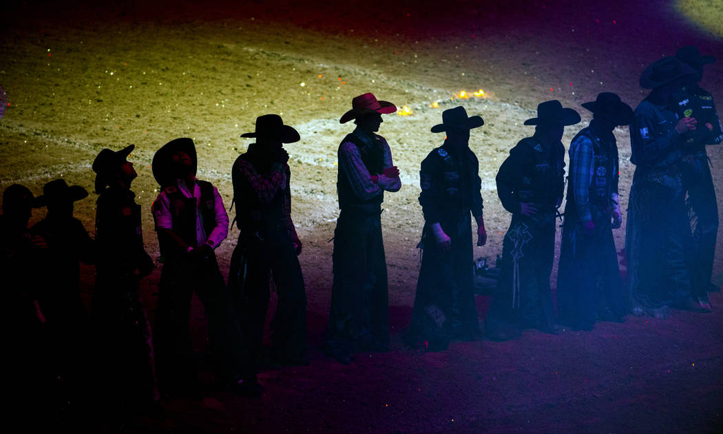 Cowboys line up while announced during opening ceremonies on the third day of the PBR World Fin ...