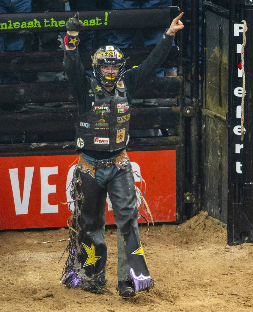Matt Triplett celebrates his successful ride on Sun Country during the third day of the PBR Wor ...