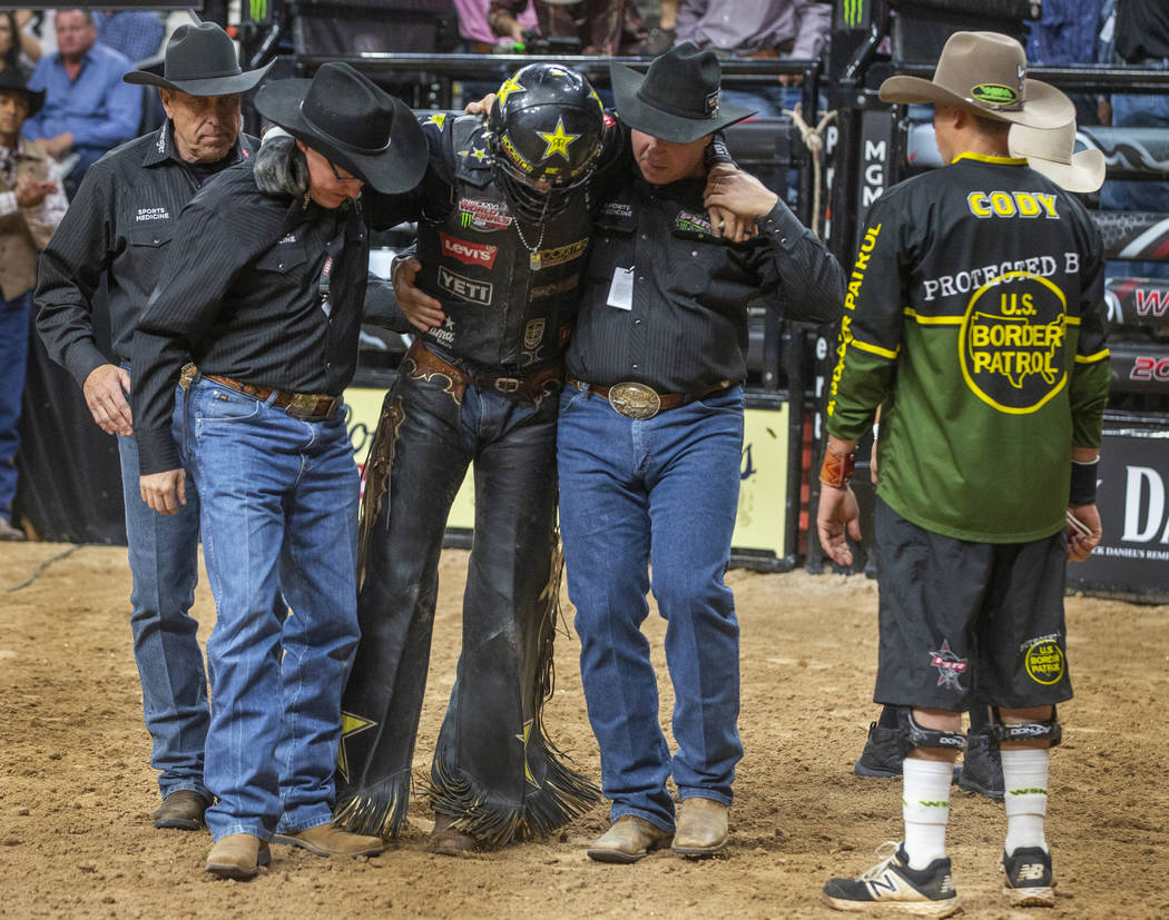 Cody Teel is assisted from the ring after riding with a torn ACL atop of Udder Lover during the ...