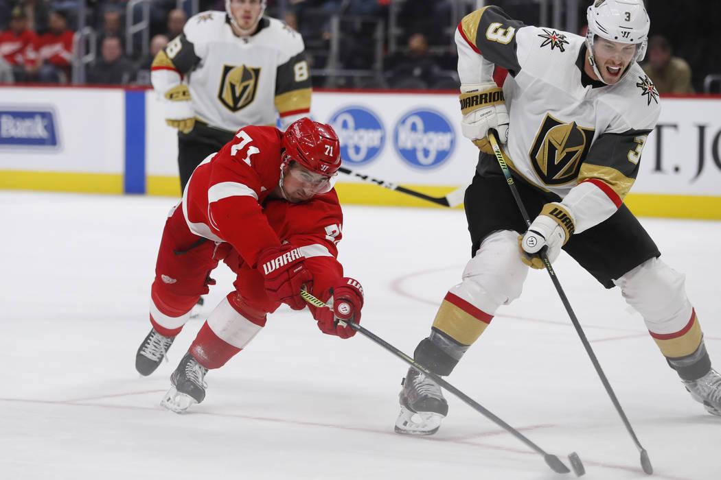 Detroit Red Wings center Dylan Larkin (71) reaches for the puck next to Vegas Golden Knights de ...