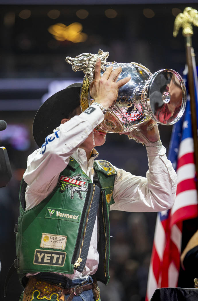 Jess Lockwood drinks a Coors beer from his winning trophy after being awarded the 2019 PBR Worl ...