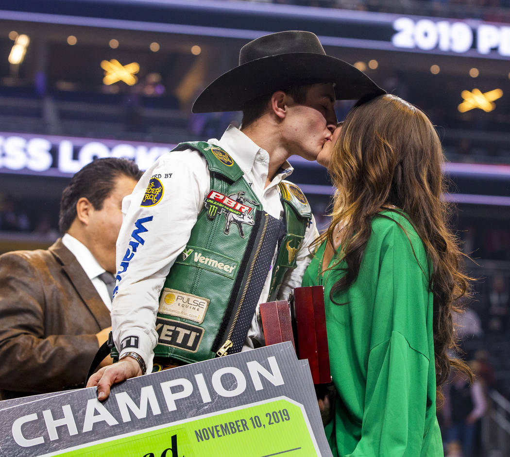 Jess Lockwood kisses his wife Hailey on stage after being awarded the 2019 PBR World Finals Cha ...
