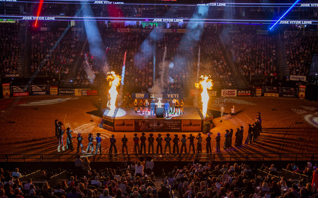 Riders are silhouetted by pyrotechnics during opening ceremonies on the last day of the PBR Wor ...