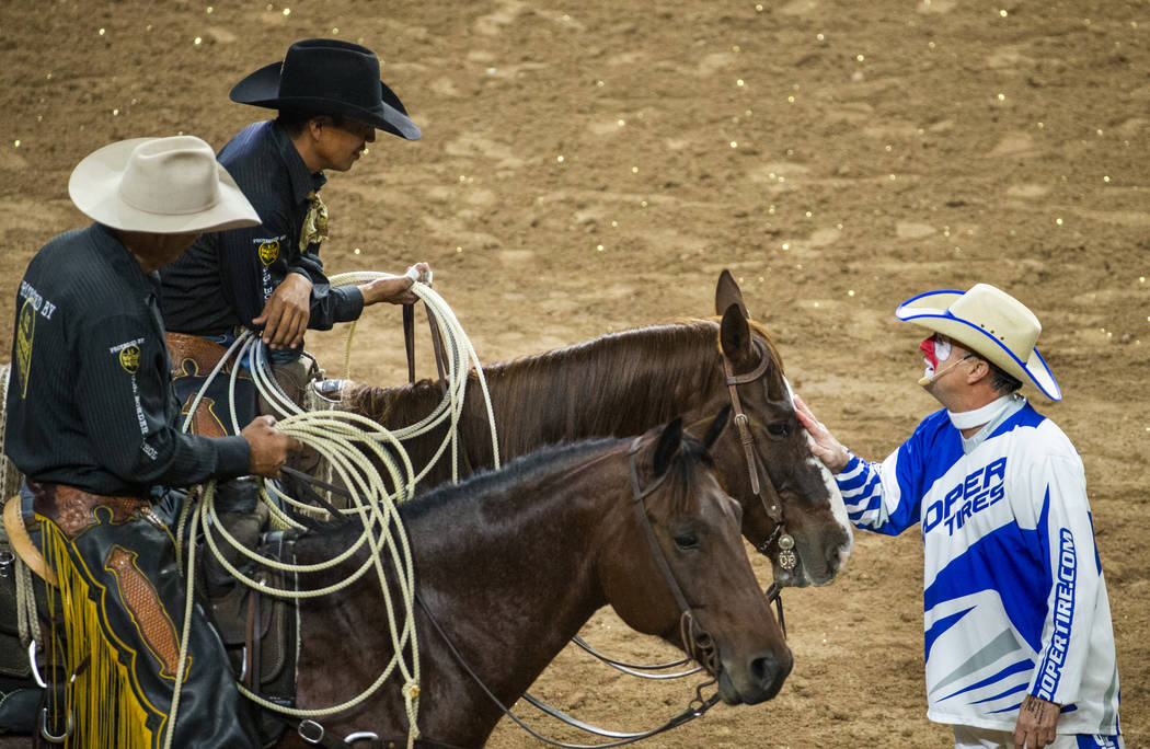 Rodeo clown Flint Rasmussen, right, jokes around with safety man Derrick Begay, top left, durin ...