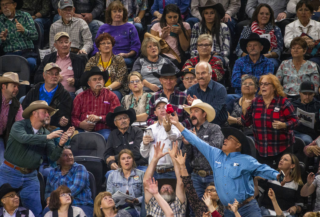 Fans reach for a free t-shirt tossed in to the crowd during the last day of the PBR World Final ...