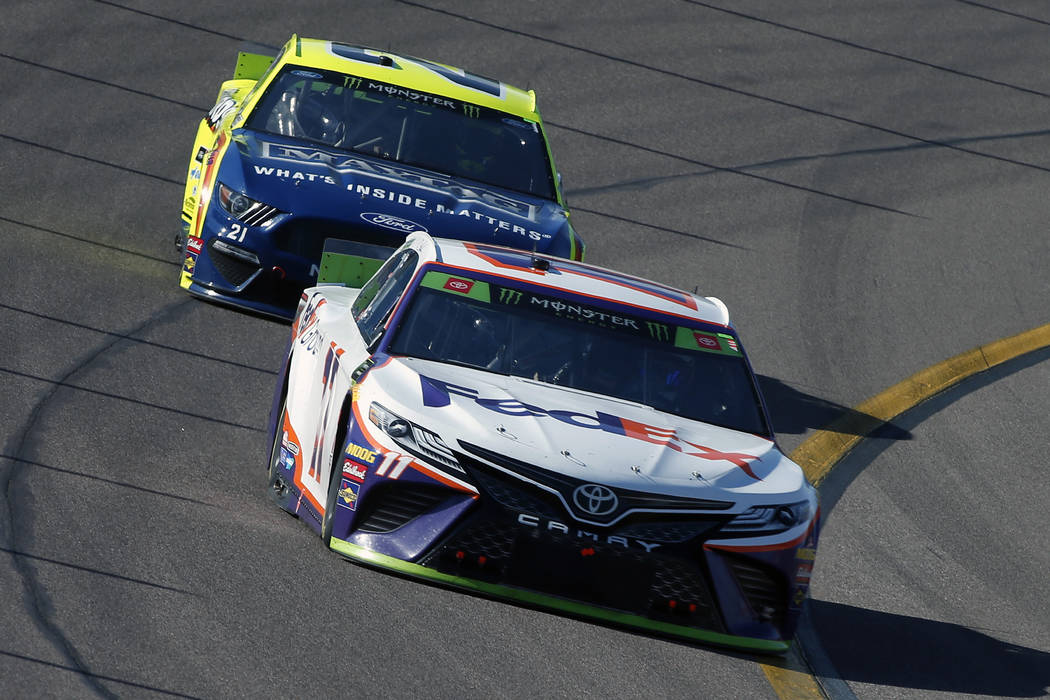 Denny Hamlin (11) drives through Turn 4 in front of Paul Menard during a NASCAR Cup Series auto ...