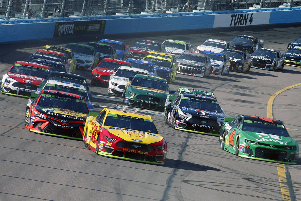 Joey Logano (22) leads the field through Turn 4 during a NASCAR Cup Series auto race at ISM Rac ...