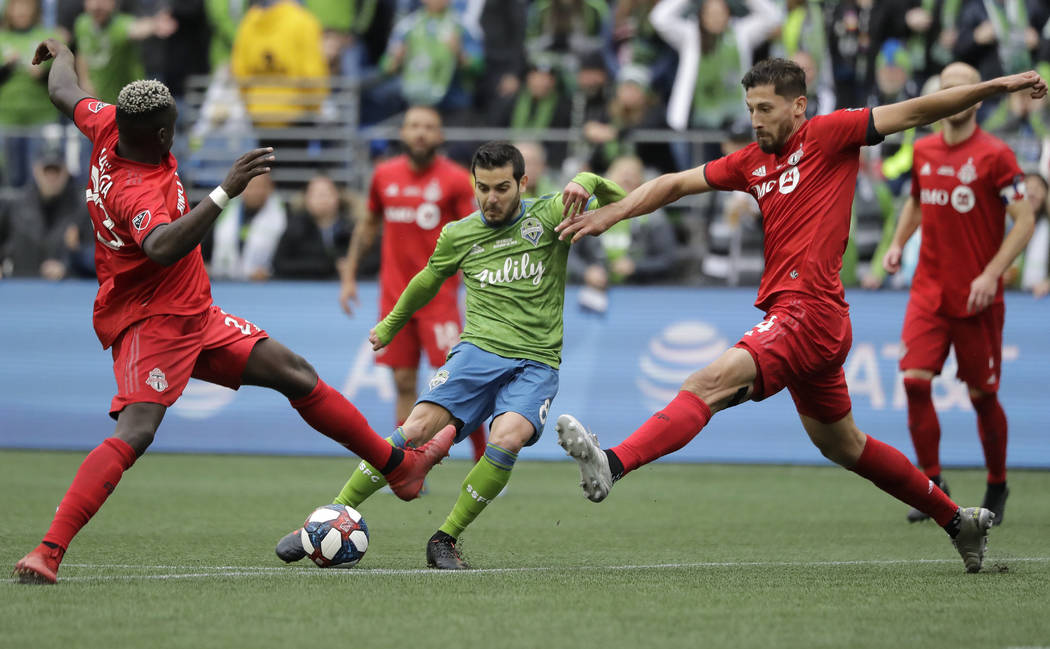 Seattle Sounders' Victor Rodriguez, center, kicks the ball to score between Toronto FC's Chris ...