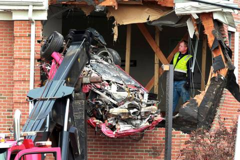 A Porsche is removed form the second story of a building after the convertible went airborne an ...