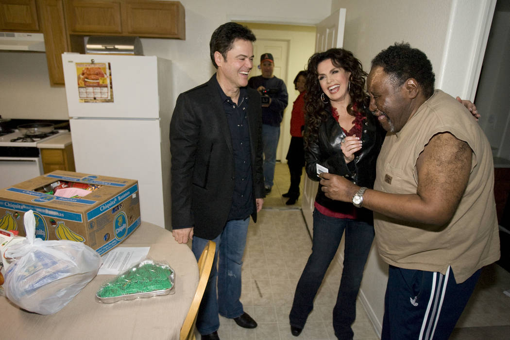 Donny and Marie Osmond deliver food to Randolph Foley, 56, at Louise Shell Senior Apartments, 2 ...