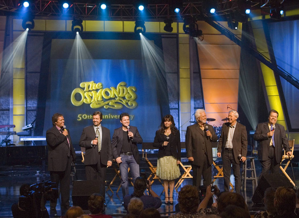 Jimmy, from left, Jay, Donny, Marie, Merrill, Wayne and Alan Osmond stand on stage during a mee ...
