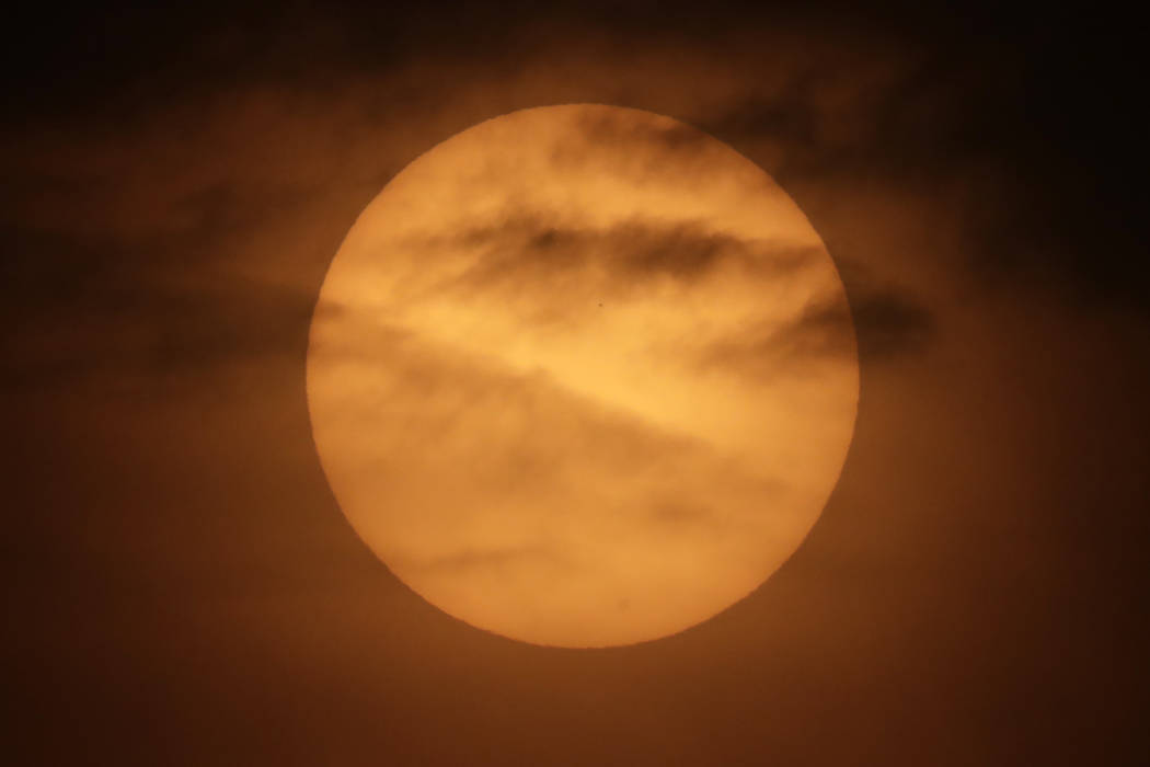 The planet Mercury is seen as a tiny dot above the mid-point of the sun during a transit across ...