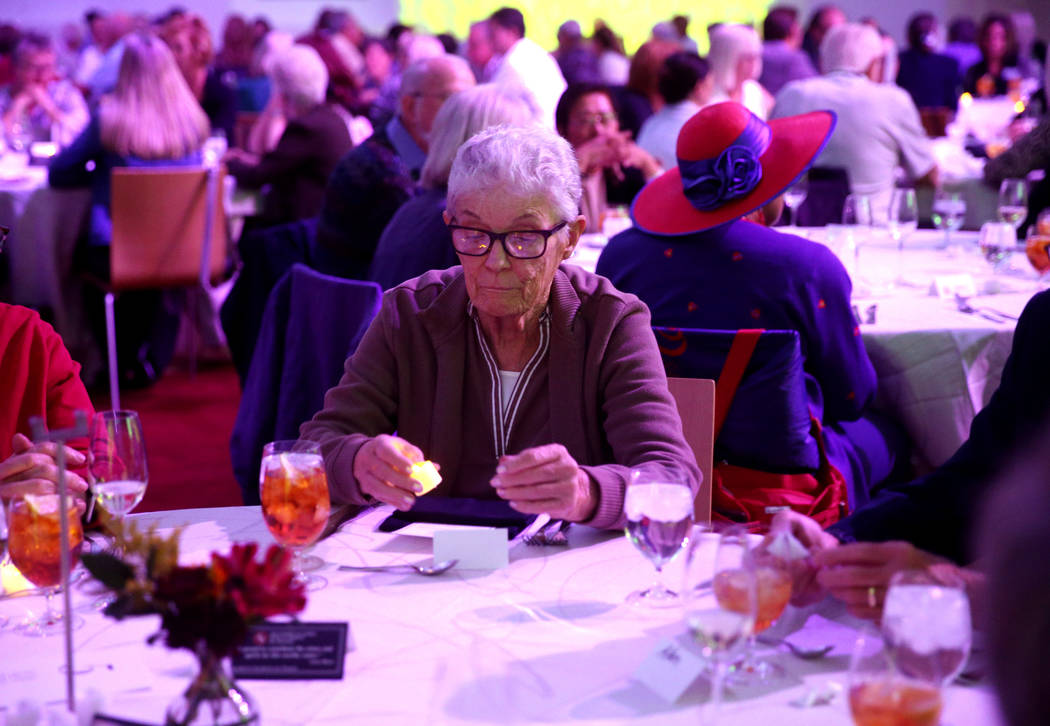 Mary Haupt of Las Vegas lights an electronic candle for a loved one during Death Over Dinner - ...