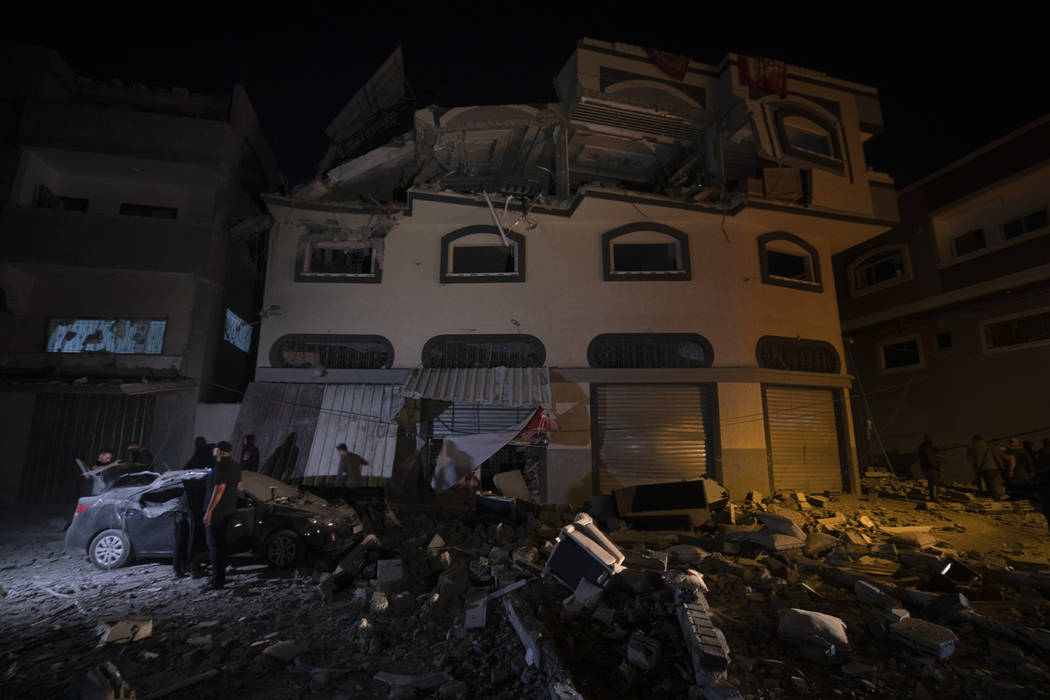 Palestinians check the damage of a house targeted by Israeli missile strikes in Gaza City, Tues ...
