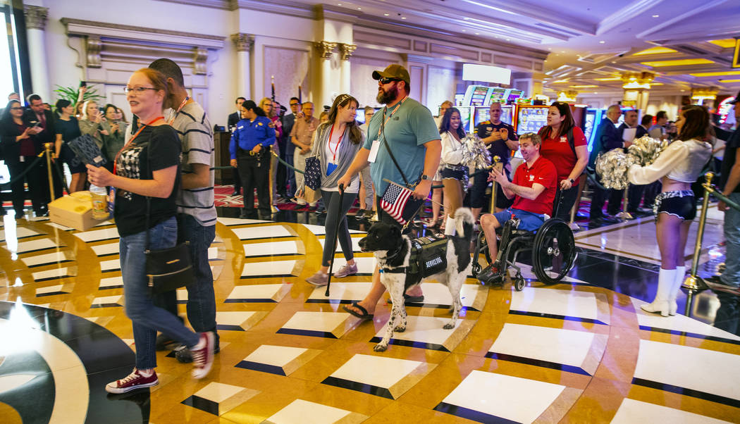 Wounded veterans and family members enter the Grand Colonnade during a 'Salute Our Troops' cere ...
