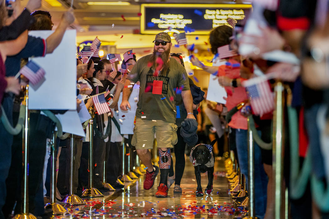 Wounded veteran Christopher Miller and his dog Zulu are celebrated by employees as makes their ...