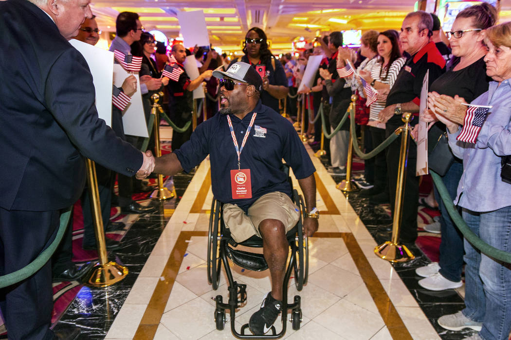 Wounded veteran Charles Armstead, center, is greeted and applauded by employees as he makes his ...