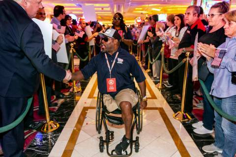 Wounded veteran Charles Armstead, center, is greeted and applauded as he makes his way through ...