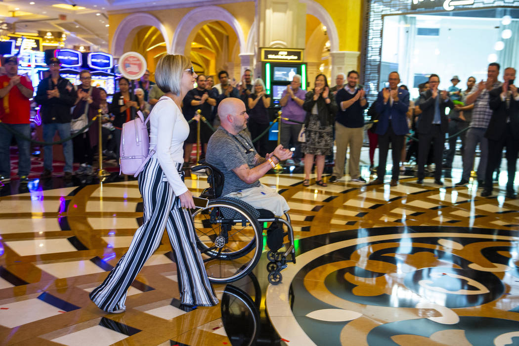 A wounded veteran, center, and family member are celebrated by employees and government officia ...