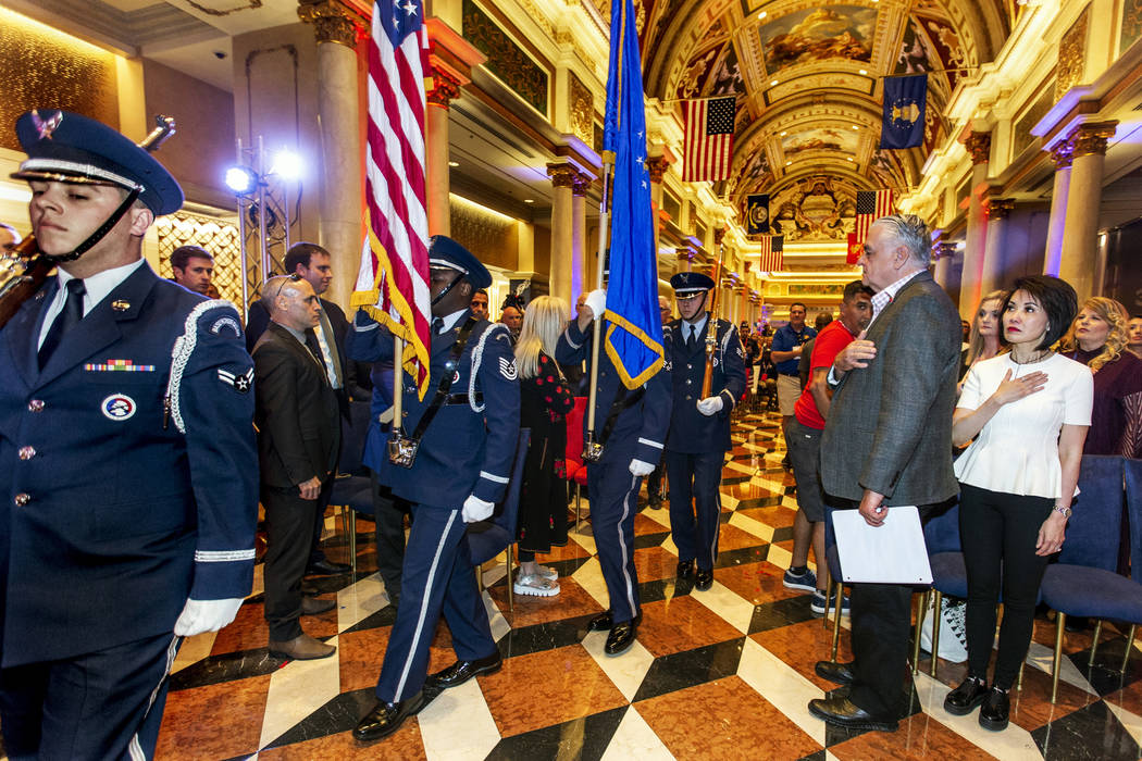 Members of the the Nellis Honor Guard bring in the colors before Gov. Steve Sisolak with his wi ...