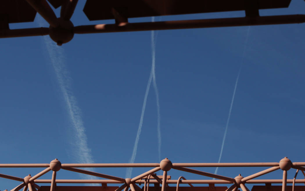 Jets flying through the blue sky leave contrails as they fly over Las Vegas on Wednesday, March ...
