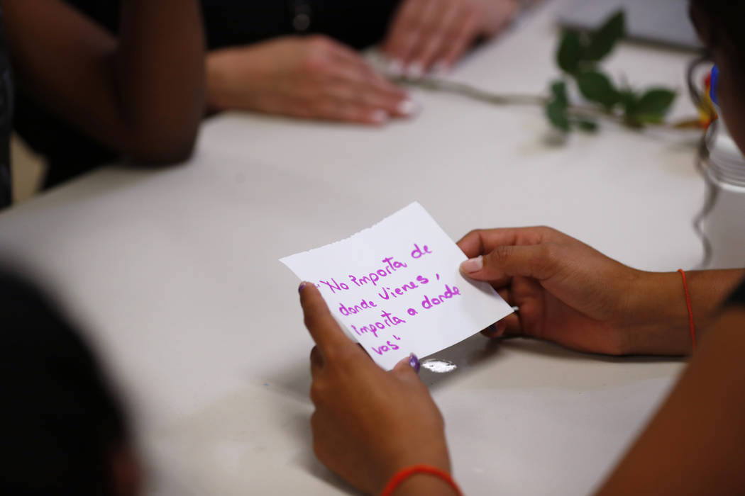 In this Sept. 24, 2019, photo, a migrant girl in U.S. government custody holds a card that says ...