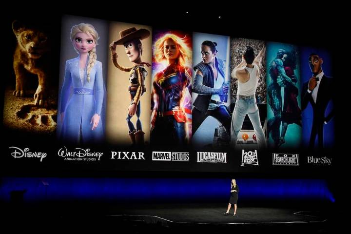 Characters from Disney and Fox movies are displayed behind Cathleen Taff of Walt Disney Studios ...