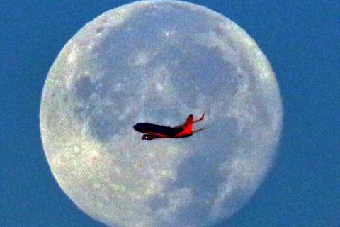 A Southwest Airlines plane flies in front of a full moon in the early morning of Wednesday, Nov ...
