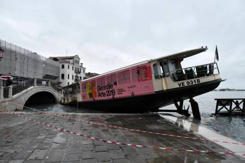 A stranded ferry boat lies on its side, in Venice, Wednesday, Nov. 13, 2019. The mayor of Venic ...