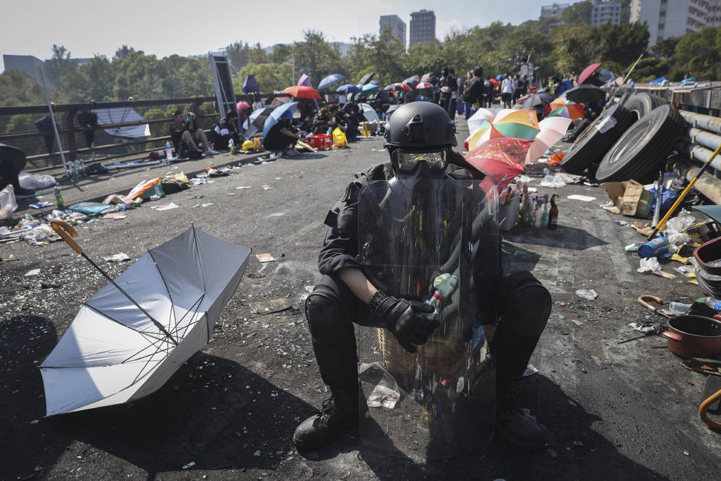 A pro-democracy protester with protection gears holds a bottle of molotov cocktail on a bridge ...
