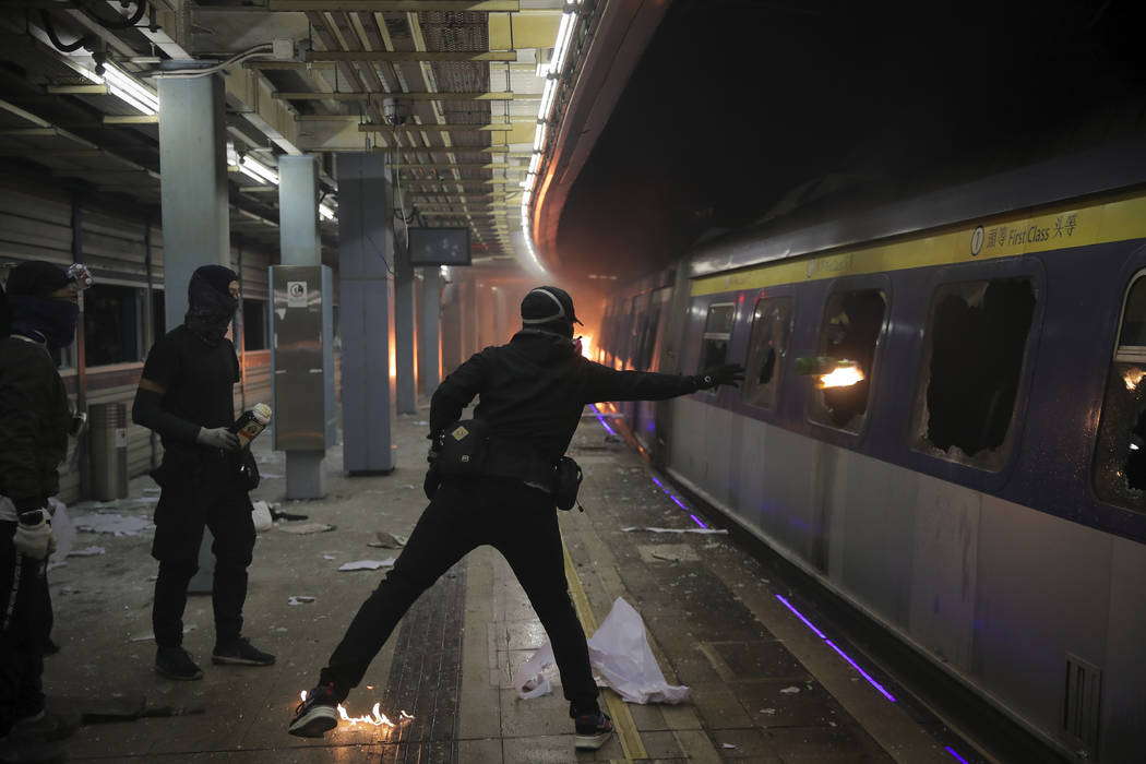 A student hurls a molotov cocktail into a train parked inside the Chinese University MTR statio ...