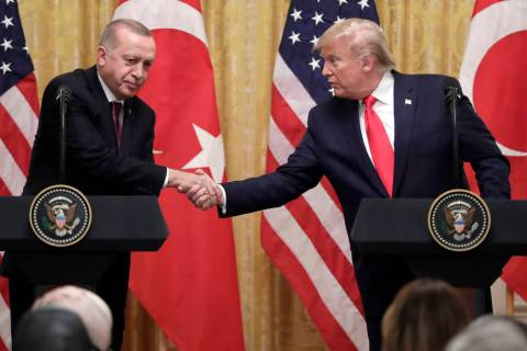 President Donald Trump shakes hands with Turkish President Recep Tayyip Erdogan during a news c ...