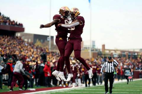 Minnesota wide receiver Rashod Bateman, right, jumps up in celebration with teammate Tyler John ...