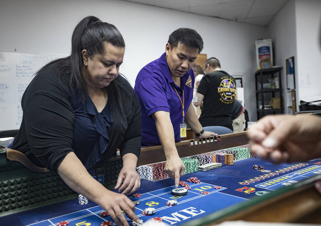 Michelle Robson, left, gets help from Alex Kim, executive director of Casino Education Group, a ...