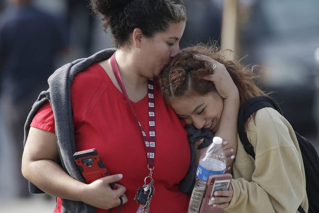 Parent Alicia Leon, left, kisses her daughter, Alejandra Cruz, a 10th grader, as they reunite a ...