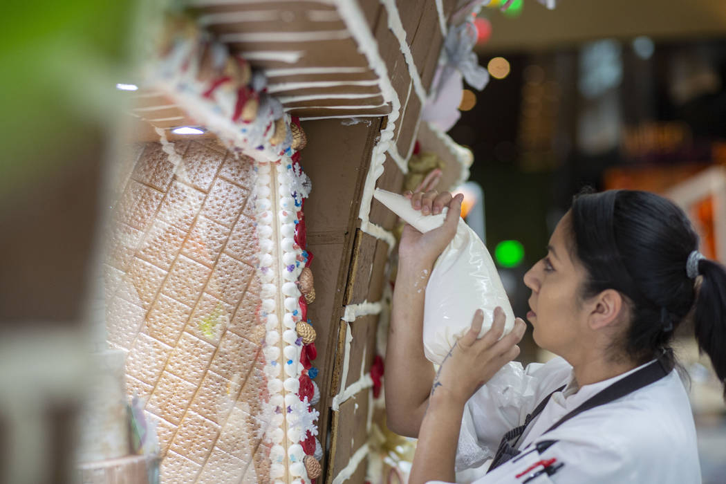 Patisserie assistant pastry chef Andrea Madrid Aria outlines gingerbread bricks with icing on t ...