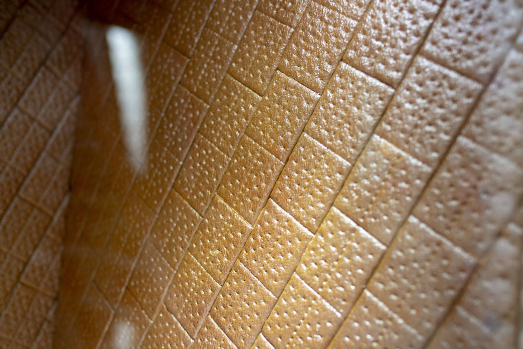 A liquor apricot luster gives shine to a graham cracker wall on a giant gingerbread house in th ...