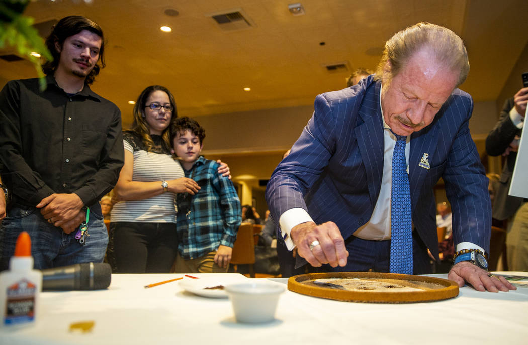 Jim Jimmerson adds flower seeds to a floragraph of his son Jacob Jimmerson who is being honored ...