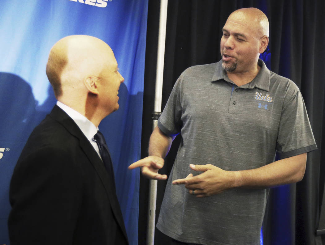 Mick Cronin, left, chats with former UCLA and NBA star Tracy Murray after Cronin was introduced ...