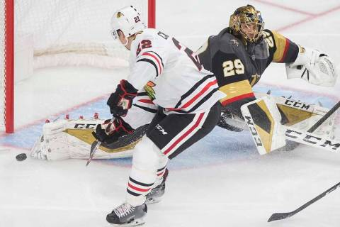Chicago Blackhawks center Ryan Carpenter (22) watches a shot from teammate Kirby Dach (77) (out ...