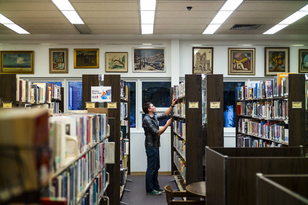 Ely Mayor Nathan Robertson, who volunteers at the local library, puts books away in Ely on Tues ...