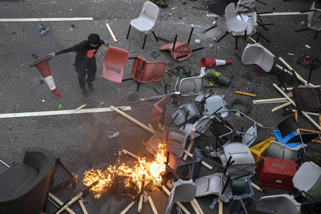 A protester tries remove plastic items from a fire burning amid debris placed to block a road l ...