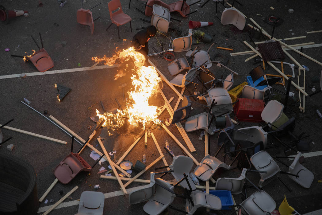 A protester tries to pour water on a fire burning amid debris placed to block a road leading to ...