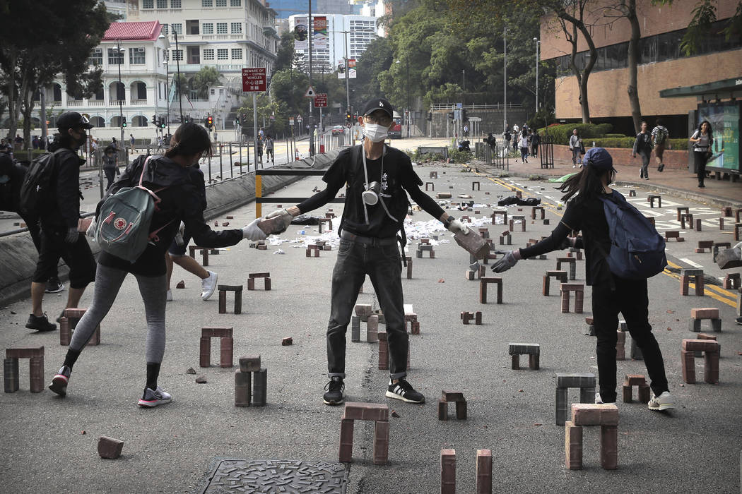 Protestors move bricks as they barricade a road near the Hong Kong Polytechnic University in Ho ...