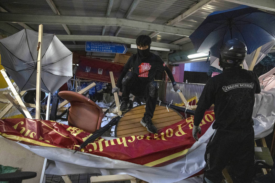 Protesters climb over a barricade on an overhead bridge near the Cross-Harbour Tunnel in Hong K ...