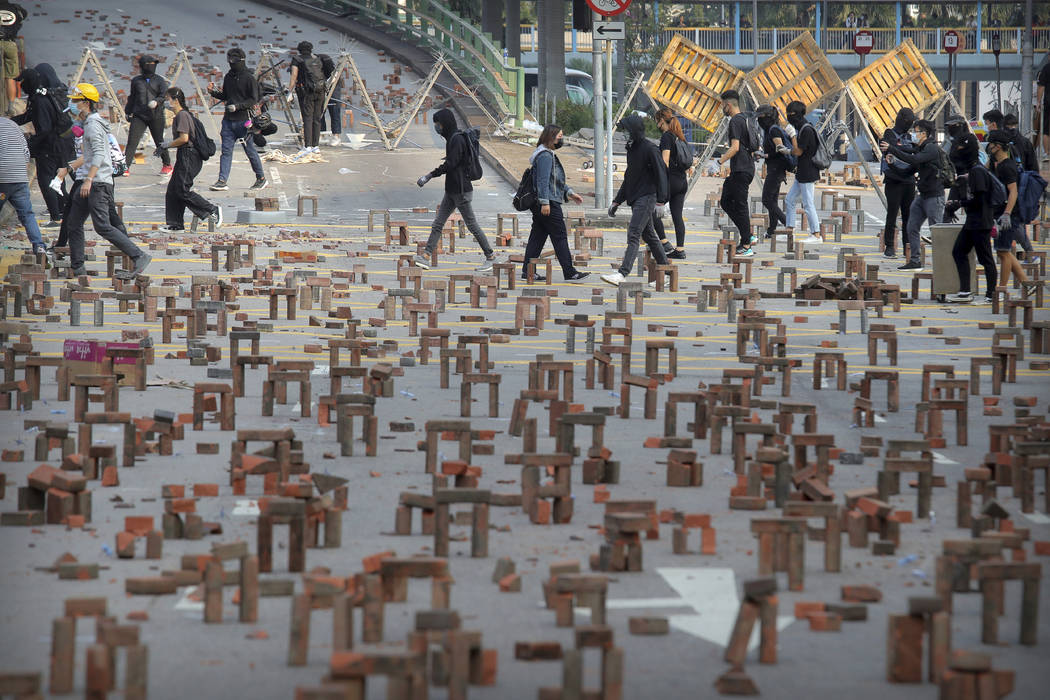 Protesters walk past barricades of bricks on a road near the Hong Kong Polytechnic University i ...